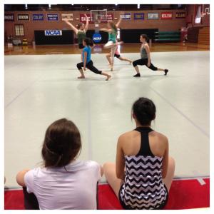 Dancers look on as their peers perform.